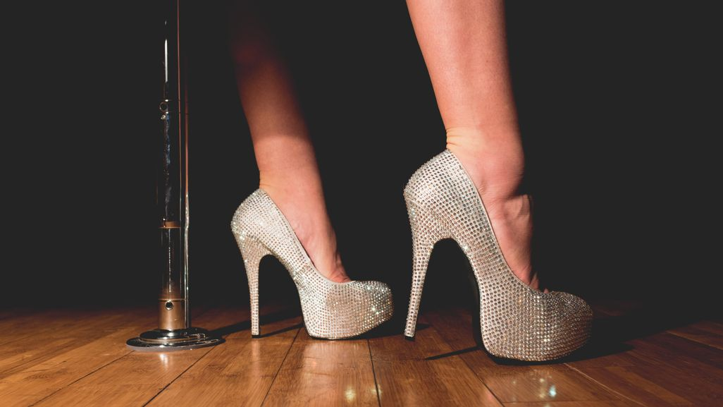 Person wearing sparkly heels standing next to a pole